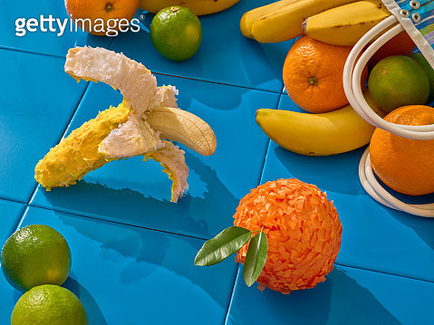 A banana and an orange shaped piñatas surrounded by fruits that have fallen from a market bag - gettyimageskorea