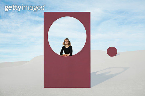 Portrait of young woman standing by maroon portal at white desert against sky - gettyimageskorea