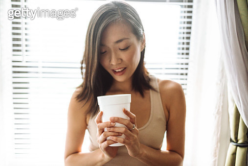 chinese woman holding the mug against the window - gettyimageskorea