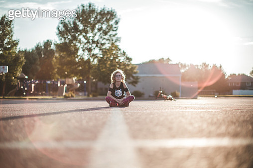 Little girl sits in the middle of an empty park parking lot as the sun shines around her and her bike she had been riding lays in the background. - gettyimageskorea