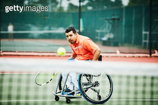 Adaptive athlete chasing down shot during wheelchair tennis match - gettyimageskorea
