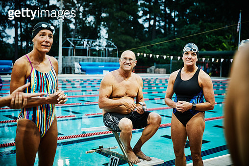Group of friends in discussion on outdoor pool deck before early morning workout - gettyimageskorea
