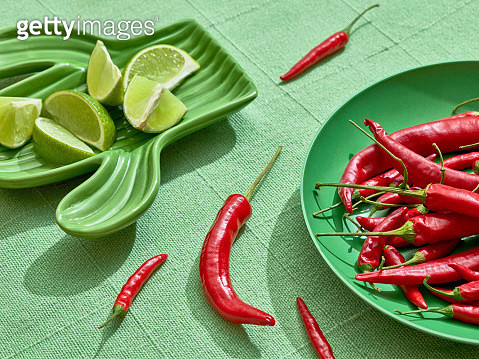 Chilli peppers and lemons over green plates and tablecloth. - gettyimageskorea