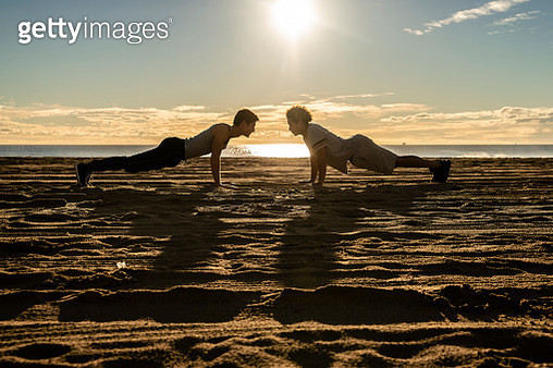 Two young friends, Latinx and Caucasian White men, doing fitness push-up workout on the beach at sunset. - gettyimageskorea