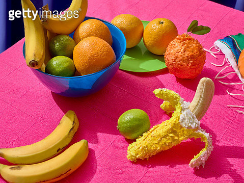 Mexican feast. Oranges, lemons and bananas in a blue bowl over a pink background - gettyimageskorea