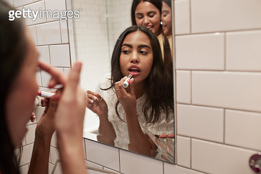 Woman applying lipstick while reflecting in mirror - gettyimageskorea