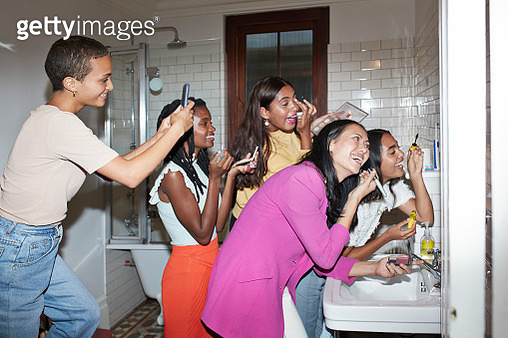 Smiling woman photographing friends doing make-up - gettyimageskorea