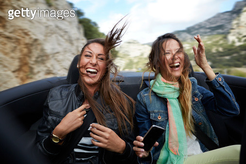 Two girls riding on backseat of car - gettyimageskorea