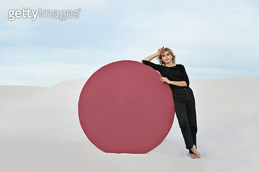 Portrait of young woman standing by circular maroon portal at white desert against sky - gettyimageskorea