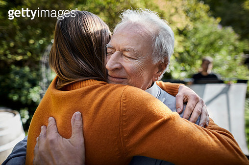 Senior man and young woman hugging in garden - gettyimageskorea