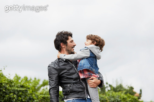 Man carrying son against clear sky - gettyimageskorea
