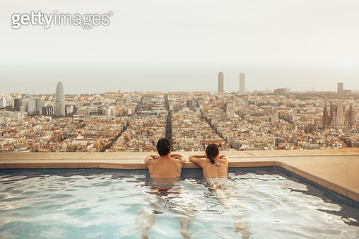 Couple relaxing on hotel rooftop looking at Barcelona city skyline. Photo composition. - gettyimageskorea