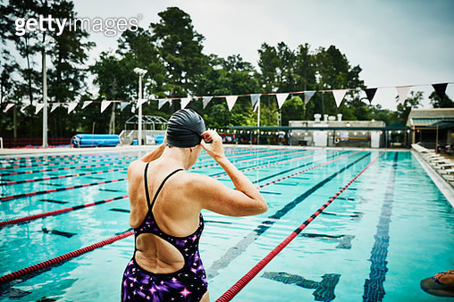 Mature woman adjusting goggles at side of outdoor pool before morning workout - gettyimageskorea