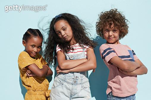 Portrait of 3 cool kids together on blue backdrop in summer - gettyimageskorea