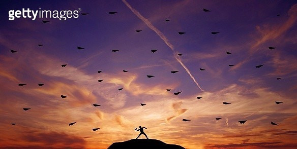 Silhouette Of Man Throwing Paper Airplanes - gettyimageskorea