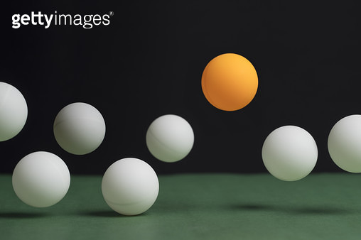Group of Table Tennis Balls bouncing. The One orange ball is higher than the white balls. - gettyimageskorea