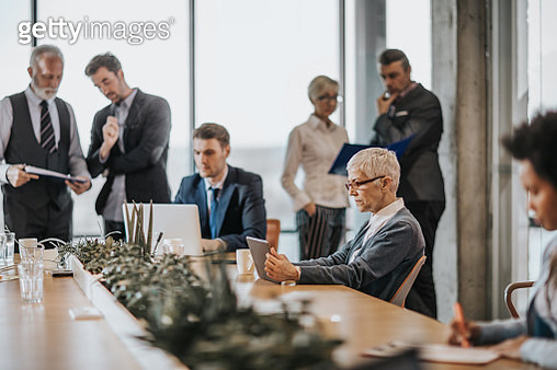 Senior businesswoman using touchpad in a full office. - gettyimageskorea