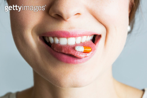 Young woman with capsule on her tongue, smiling - gettyimageskorea