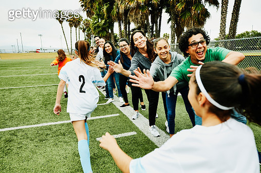 Young female soccer players high fiving parents on sidelines after soccer game - gettyimageskorea
