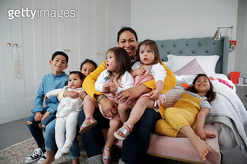 Single mother with six children sitting on bed, smiling towards camera, happiness, togetherness - gettyimageskorea