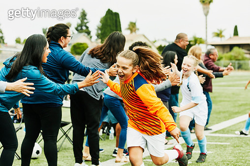 Young female soccer goalie high fiving parents on sidelines after soccer game - gettyimageskorea
