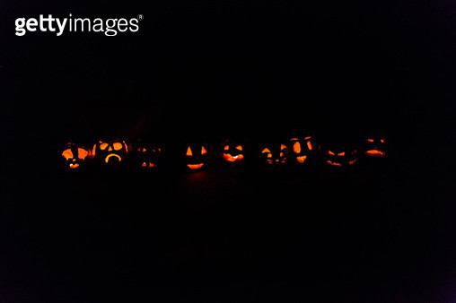 multiple jack o' lanterns lined up outside in the dark with their faces lit with candles for light - gettyimageskorea