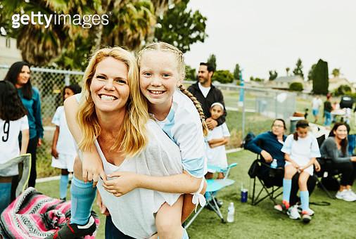 Smiling mother giving daughter piggy back ride on sidelines after soccer game - gettyimageskorea