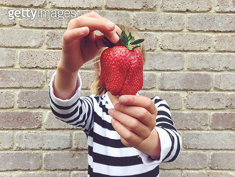 Child holding large strawberry in front of face - gettyimageskorea