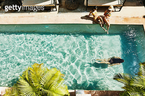 Overhead view of female friends seated next to outdoor hotel pool as friend swims underwater - gettyimageskorea