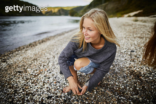 Smiling blond young woman at the riverbank - gettyimageskorea