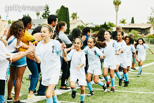 Young female soccer team giving high fives to parents on sidelines after game - gettyimageskorea