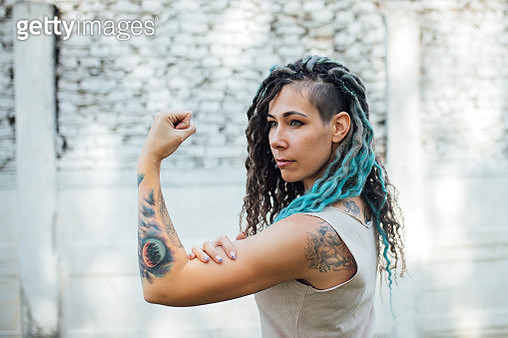 Original beautiful young woman with blue dreadlocks and a shaved temple in tattoos shows strength, feminism, girl power - gettyimageskorea