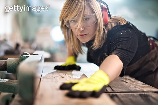 Blonde woman cutting a plank - gettyimageskorea