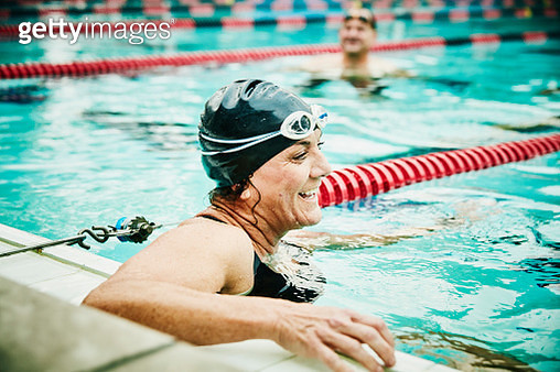 Laughing mature swimmer resting between sets of early morning workout in outdoor pool - gettyimageskorea