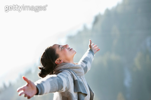 Woman with head back and arms outstretched - gettyimageskorea