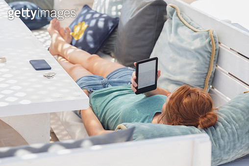 Young woman reading e-book, lying on bench - gettyimageskorea