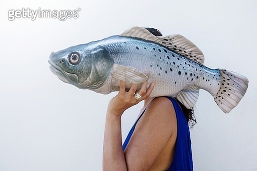 Close-Up Of Woman Holding Fish Against White Background - gettyimageskorea