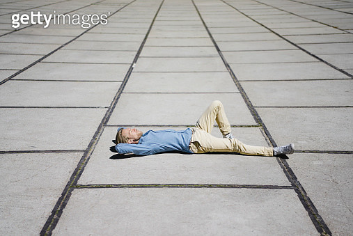 Young man lying on a square - gettyimageskorea