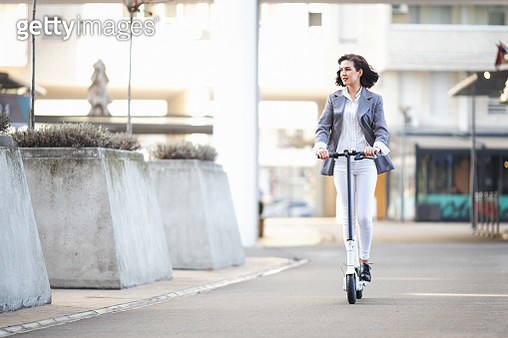 Businesswoman on e scooter in the city - gettyimageskorea