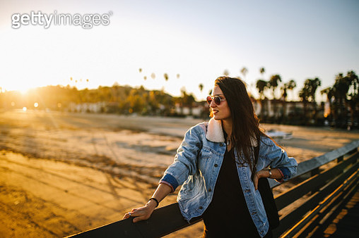 Beautiful sunset above the Santa Barbara boardwalk. Portrait of a brunette woman, enjoying the ocean view. She is wearing fashionable, retro styled streetwear, a denim jacket and sunglasses, under the California sunshine. - gettyimageskorea