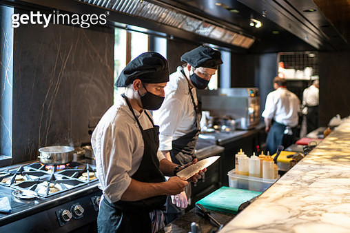 Chefs wearing protective face masks working together in restaurant kitchen - gettyimageskorea