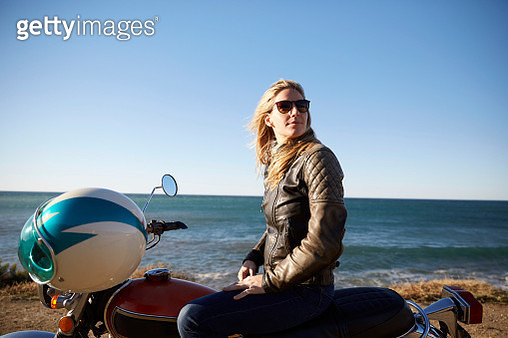 Portrait of young woman with motorcycle - gettyimageskorea