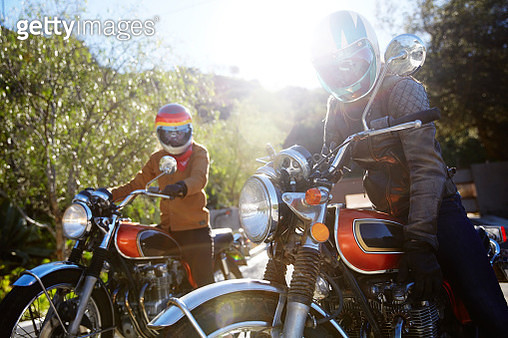 Two young women riding motorcycles on empty road - gettyimageskorea