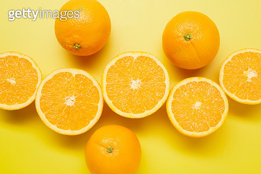 Still life of sliced oranges on yellow background - gettyimageskorea
