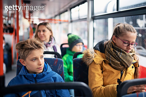 Kids travelling to school by bus or tram. Girl is checking her smartphone. Her brothers are looking out of window. Autumn time, kids are wearing warm clothing.Nikon D850 - gettyimageskorea