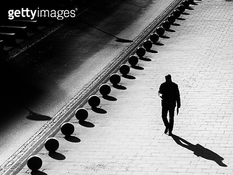 High Angle View Of Silhouette Man Walking On Sidewalk - gettyimageskorea