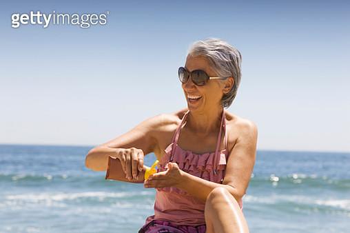 Hispanic woman applying sunscreen on beach - gettyimageskorea