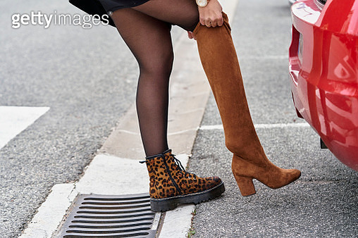 Woman changing her footwear while standing next to her car outdoors on the street. - gettyimageskorea