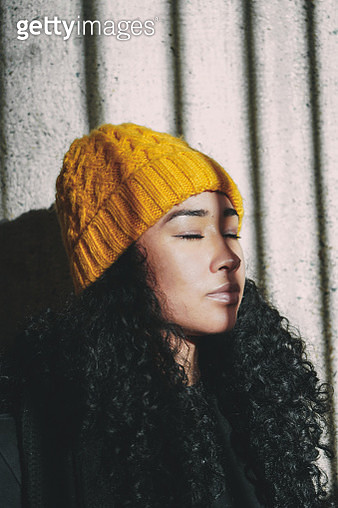 Young woman wearing a yellow toque enjoys the sun outside - gettyimageskorea