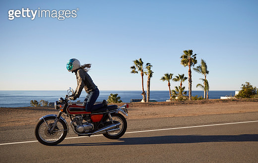 Young woman riding motorcycle on empty road - gettyimageskorea